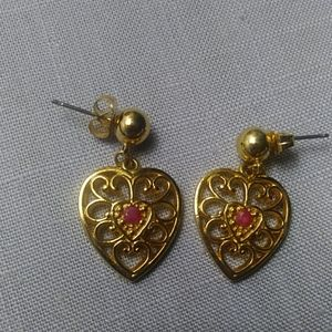 Gold heart earrings with red stone in center.